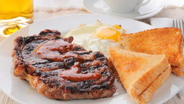 Steak, sunny side up eggs and toast