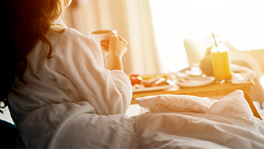 woman drinking coffee in hotel bed