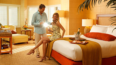Man and woman drink champagne in Tropicana hotel room.
